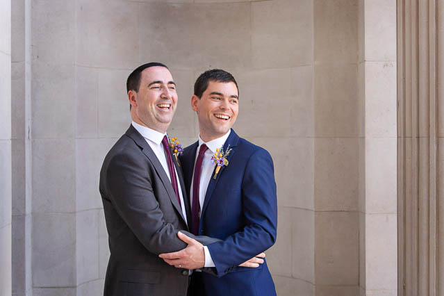 Two grooms pose for portraits outside Marylebone Old Town Hall in central London.