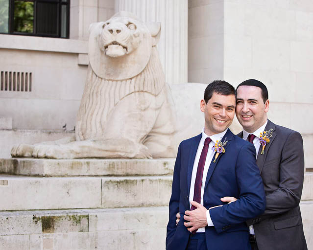 Two grooms stand outside Marylebone Old Town Hall after their civil wedding ceremony in the Mayfair Room.