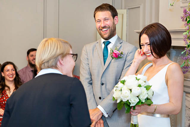 A new bride and groom receive congratulations from the Westminster registrar in the Soho Room after their wedding.
