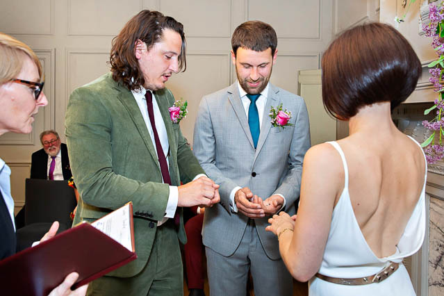 A man in a green suit brings the groom his bride's wedding ring.