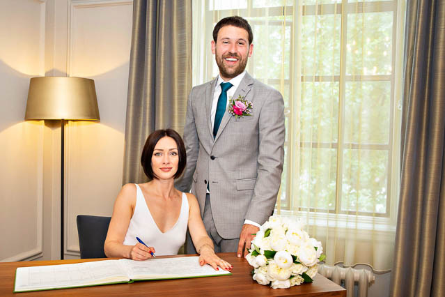 Westminster City Council's Soho Room in Marylebone Old Town Hall: the new Mr and Mrs sign the marriage register, completing their paperwork.