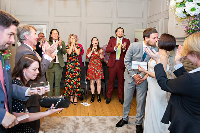 Wedding guests clap while the newlyweds kiss after their civil marriage ceremony in the Soho Room, London.