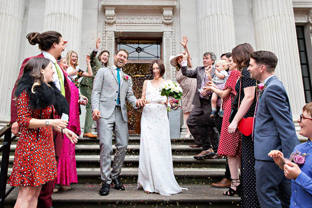 The bride and groom walk down the steps of Old Marylebone Register Office with their guests throwing confetti.