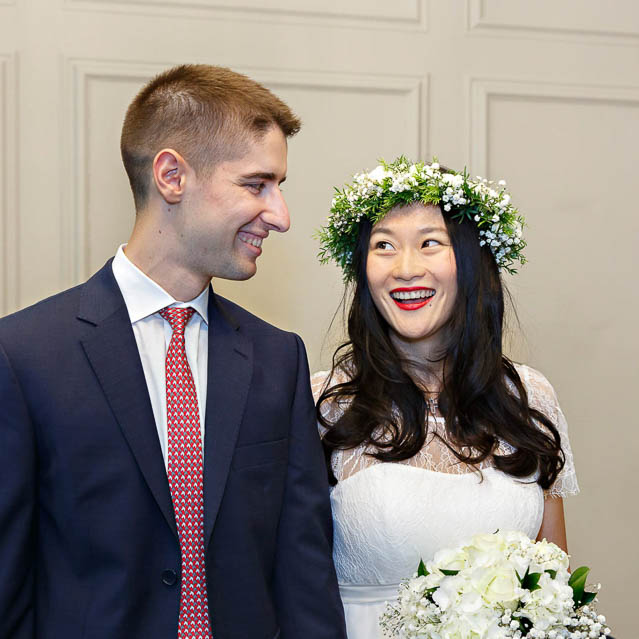 A Chinese bride and her British groom exchange smiles during their civil marriage ceremony in the Soho Room at Marylegone Old Town Hall.