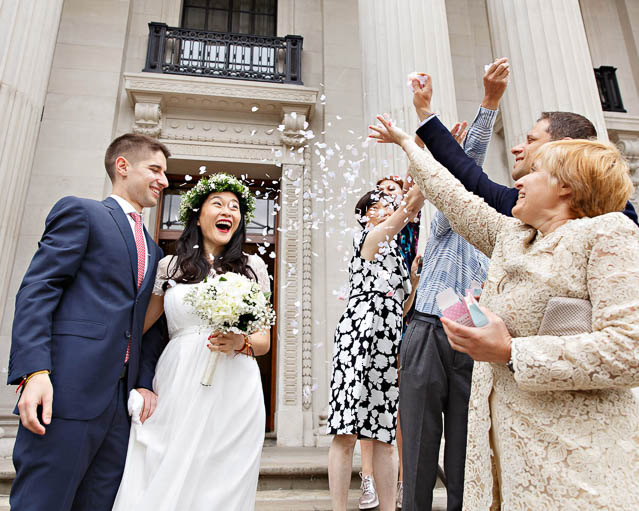 Guests throw confetti over the bride and groom in Marylebone, but most of the confetti misses.