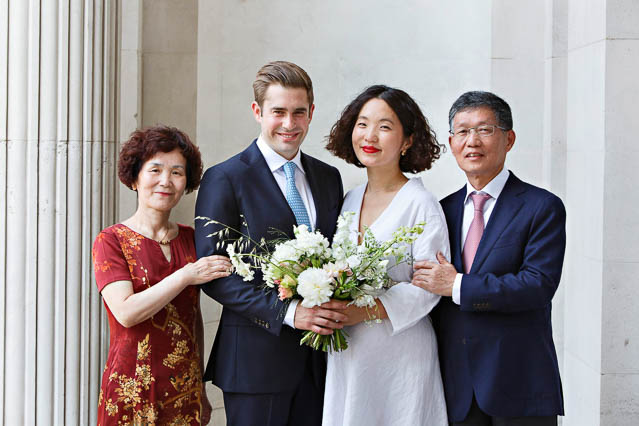 A family wedding photo of the bride, groom and her parents taken on the top step at Old Marylebone Town Hall in central London.