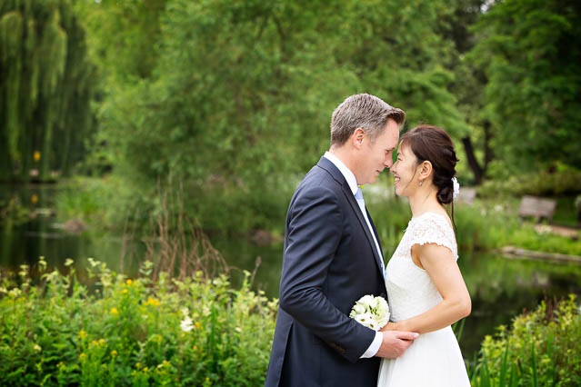 A bride and groom pose together in Regents Park for couple portraits after their wedding at Marylebone Old Town Hall.