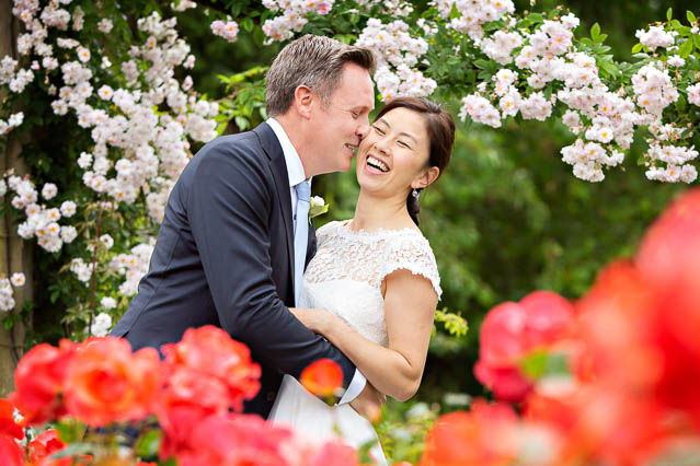 A bride and groom kiss in Regents Park for their summer wedding photos.