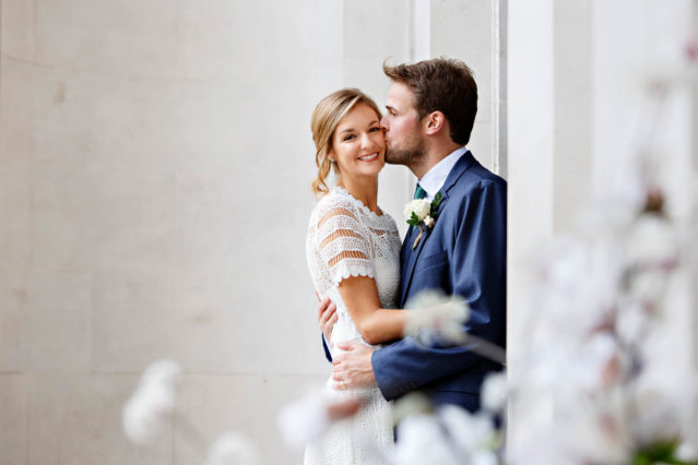 Natural light wedding portraits of the bride and groom on the top step of Old Marylebone Town Hall in central London.