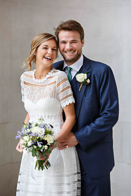 A bride in a short white lace dress and a groom in a blue suit pose for wedding photos on the steps of Old Marylebone register office.