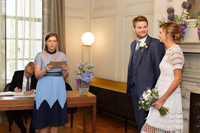 A wedding guest does a reading while the bride and groom listen. The civil wedding ceremony is taking place in the Pimlico Room at Old Marylebone Town Hall.