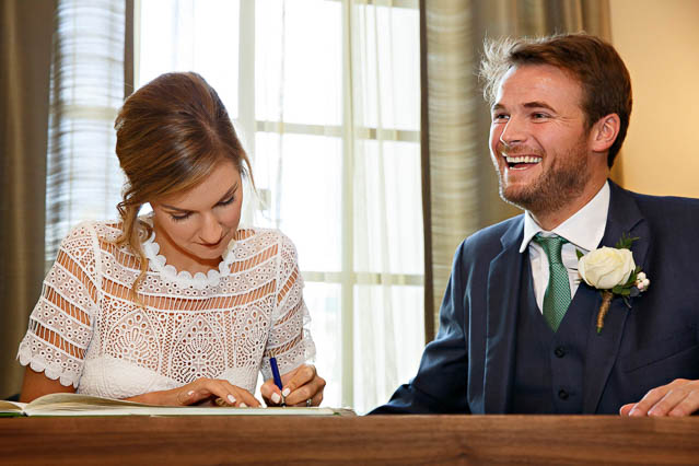 The bride and groom sign the register - paperwork for their civil marriage in Marylebone.