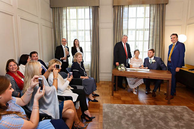 Guests photograph the bride and groom during their civil marriage ceremony in the Pimlico Room at Old Marylebone Town Hall in central London.