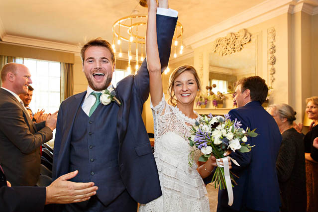 The bride and groom walk out of their civil wedding ceremony with their arms held high in celebration.