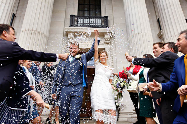 The bride and groom leave Old Marylebone Town Hall with their arms held high in celebration while their guests throw colourful confetti.