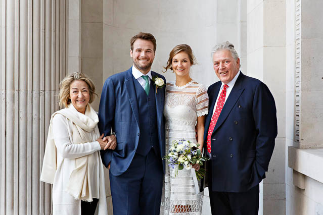 The newlywed couple stands with family members outside Old Marylebone Town Hall for wedding photos.