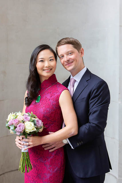A bride in a bright pink wedding dress poses for a wedding portrait with her husband.