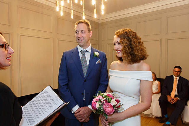 A bride in a shoulder-baring full-length white bridal gown and a groom in a blue suit in the Soho Room for their wedding.
