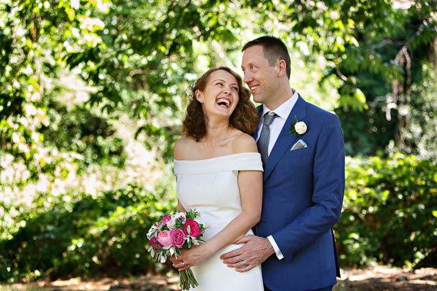 A groom wearing a dark blue suit makes his new bride laugh in Regents Park, London.