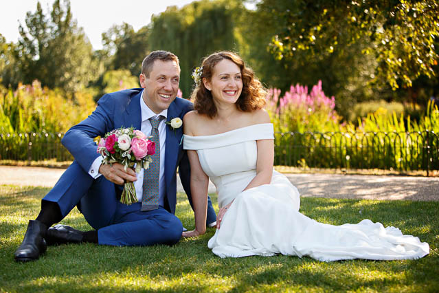 A bride and groom sit on the grass in Regents Park while the groom holds a pink bouquet.