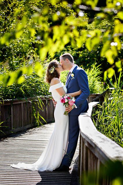 A new husband and wife pose for portraits on a bridge in Regents Park, Marylebone, London.