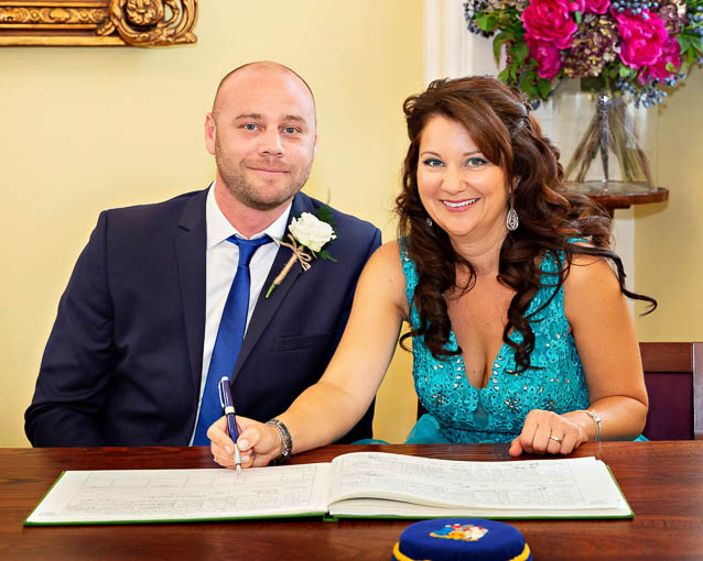 A bride in a blue wedding gown and a groom wearing a dark blue tie sign the register after their marriage in one of Chelsea Registry Office rooms.