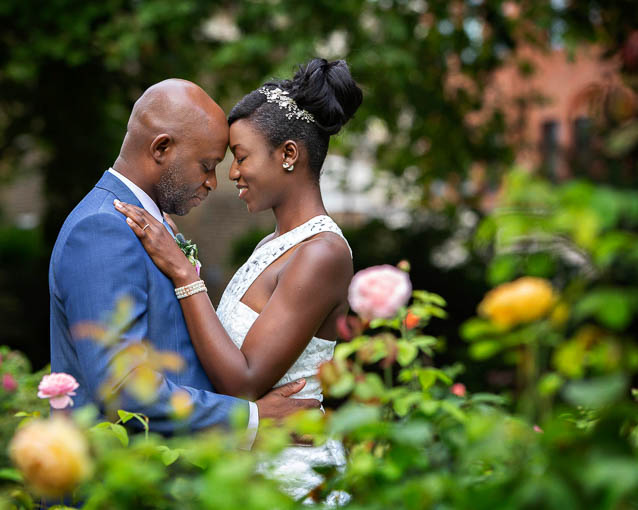 This bride and groom pose for photos in a rose garden after their registry office London civil marriage.