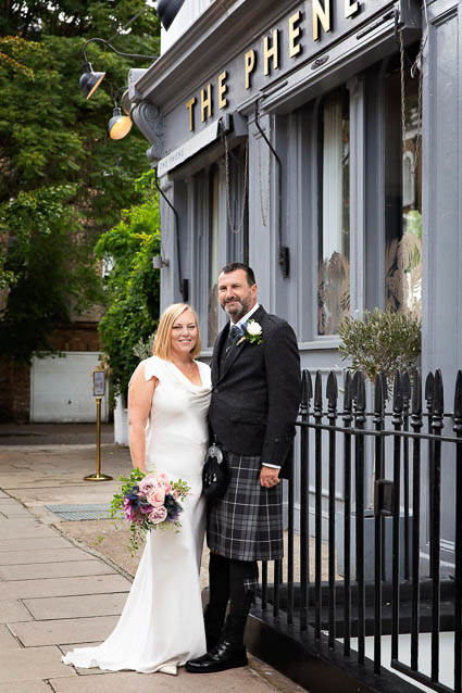 A bride and groom stand outside The Phene, where they held their wedding reception.