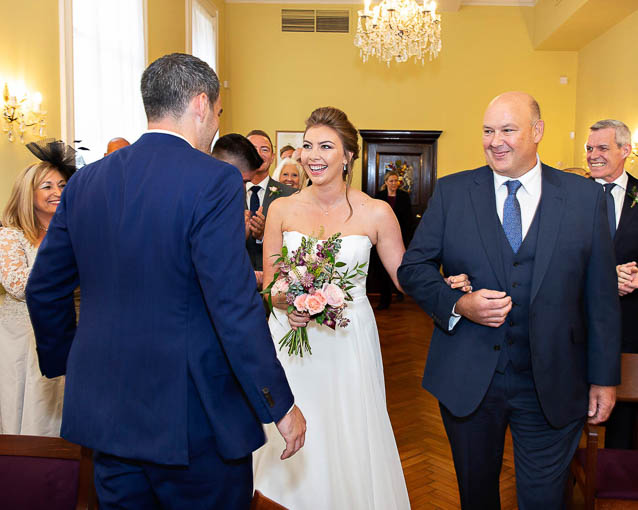 A bride walks into the Brydon Room on the arm of her father to meet her groom.