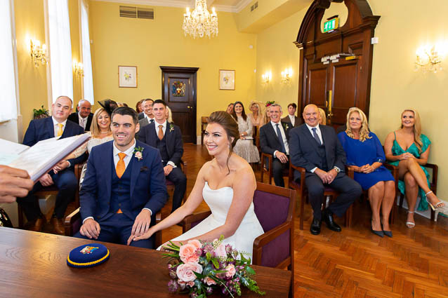 The bride and groom sit at the front of the Brydon Room in Chelsea Town Hall in front of their guests.