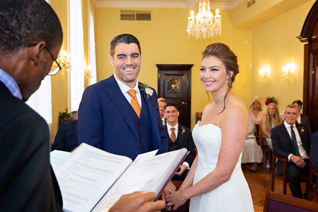 A bride and groom exchange wedding vows in the Brydon Room in Chelsea Town Hall on Kings Road, London SW3.