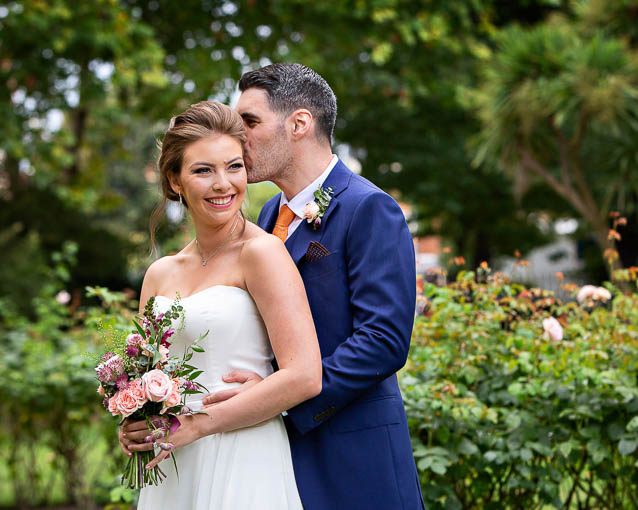 A groom and bride holding a pink and plum bouquet have portraits in gardens in the Royal Borough of Kensington and Chelsea.