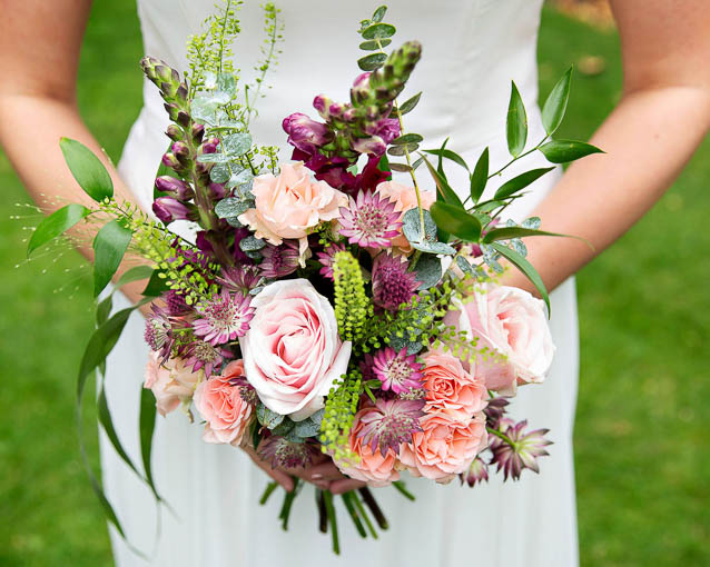 A beautiful small summer wedding bouquet for an elopement. It has pinks and plum colours.