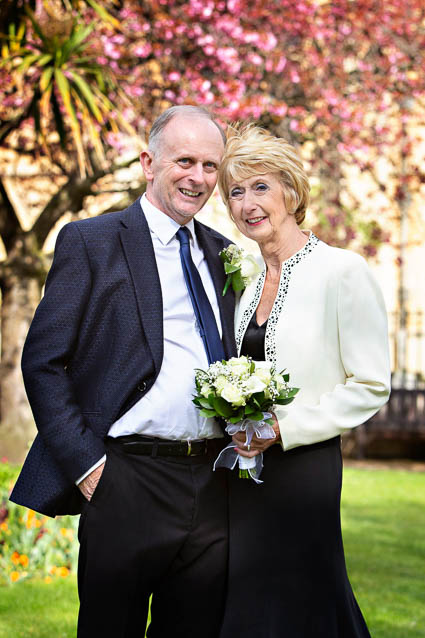 An older bride and groom pose for wedding portraits in a garden near Chelsea Old Town Hall, London.