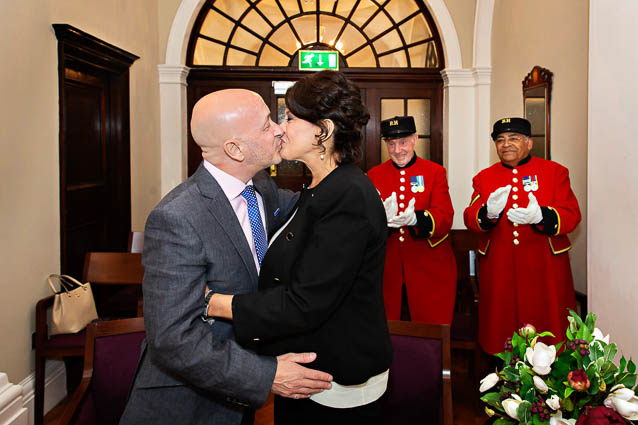 Newlyweds kiss after being announced man and wife in Chelsea Town Hall, London. They're watched by red-suited Chelsea Pensioners.