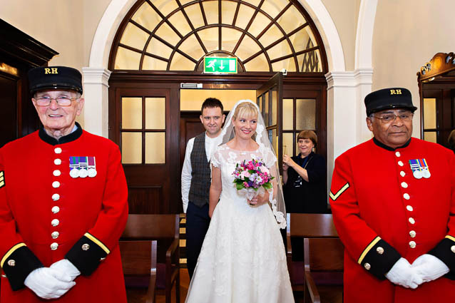 The bride and groom enter the Harrington Room for their wedding witnessed by two Chelsea Pensioners.