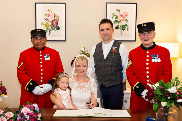 Two Chelsea Pensioners act stand next to the bride and groom during their civil marriage ceremony sign of the register in the Harrington Room.