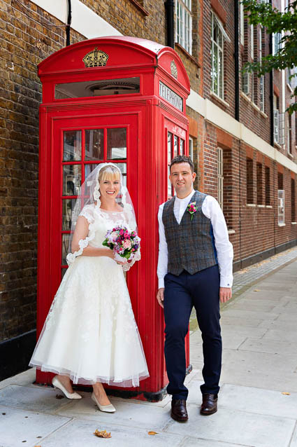 A groom and a bride in a white lace dress and veil have their wedding photo outside a red London phone box in Chelsea.
