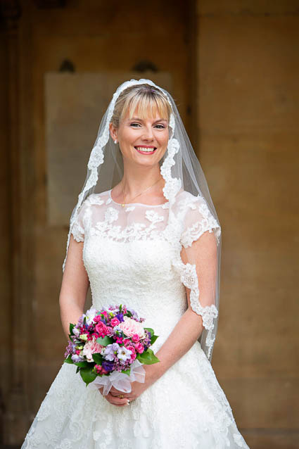 A bride wears a white full-length lace wedding gown and holds a wedding bouquet with pink and purple flowers.