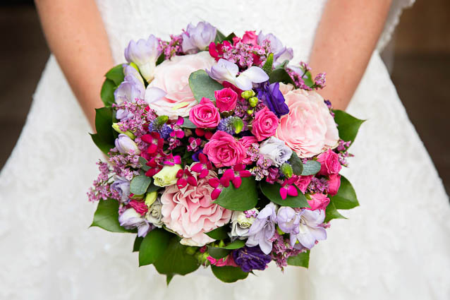 A wedding bouquet of bright pink, mauve, pastel pink and purple flowers for a summer wedding.