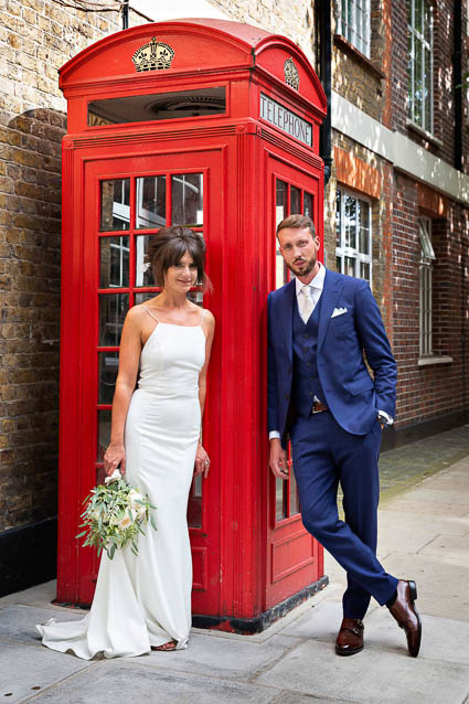 A bride and groom pose near a red telephone box after their Chelsea Old Town Hall Registry Office civil wedding.