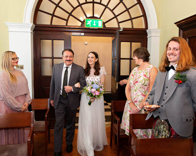 A bride and her father walk into one of the Chelsea Registry Office rooms for her wedding to a Scottish groom.