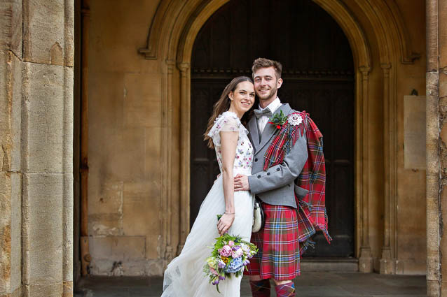 A bride in a long white dress and floral sprigged bodice stands with her new husband in a red tartan kilt after their wedding at Chelsea Old Town Hall Registry Office.