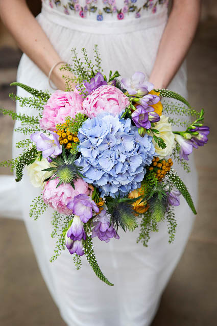 A bride holds a summer wedding bouquet with pastel colours.