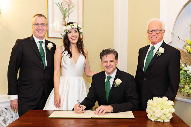 The Chelsea Registry Office wedding ceremony of this bride and groom: they're standing with their two witnesses after the signing.
