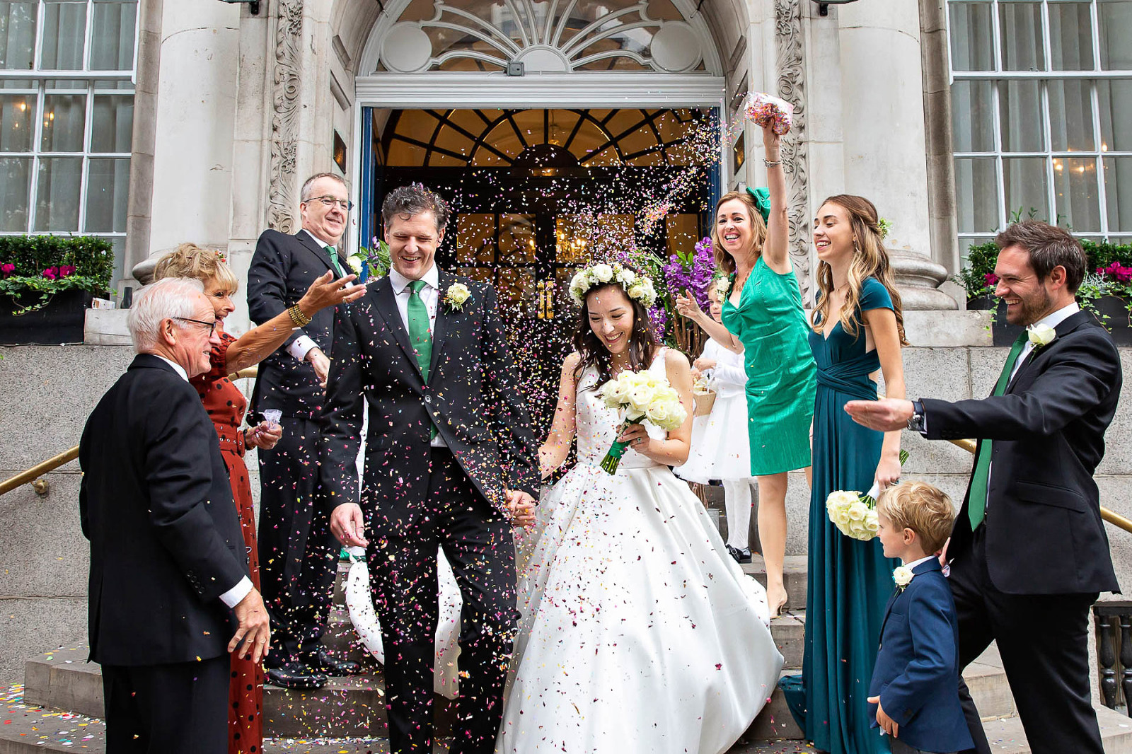 A bride and groom walk down Chelsea Town Hall's steps on the Kings Road in a burst of confetti after their civil wedding.