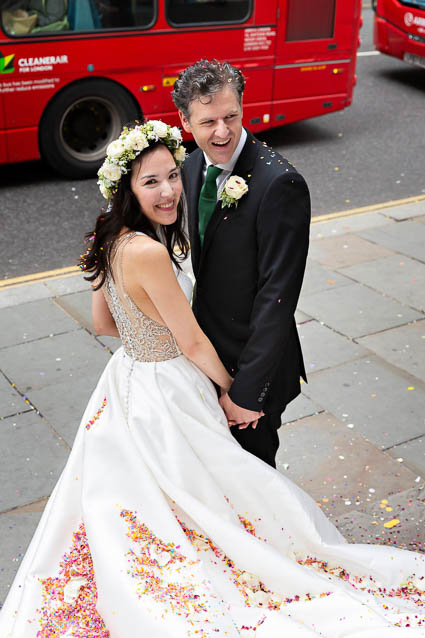 A bride and groom stand hand in hand on the Kings Road steps of RBKC Town Hall.