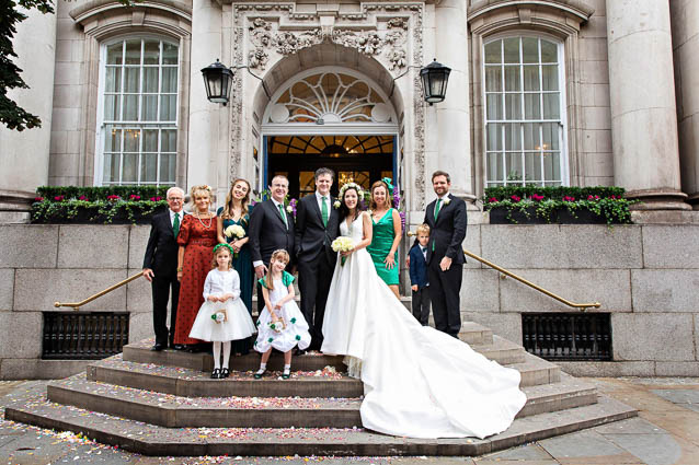 A bride and groom and the bridal party stand on Kings Road steps after their Chelsea Old Town Hall wedding.