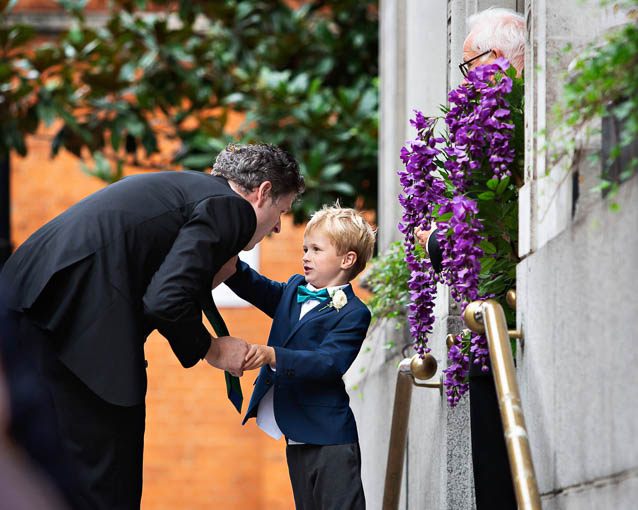 A small boy in a blue suit and green bow tie asks one of the groomsmen a question. They're at a Chelsea Old Town Hall wedding.